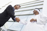 A Middle Eastern businessman shaking hands with a Caucasian busi — Stock Photo