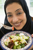 A Middle Eastern woman with a plate of salad — Stock Photo