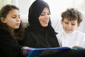 A Middle Eastern family reading a book together — Stock Photo