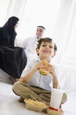 A Middle Eastern boy enjoying a fast food burger meal — Stock Photo