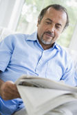 A Middle Eastern man reading a newspaper at home — Stock Photo
