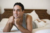 A Middle Eastern man lying on a bed — Stock Photo