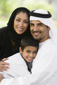 A Middle Eastern couple and their son sitting in a park — Stock Photo