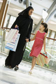 A Middle Eastern woman with a girl in a shopping mall — Stock Photo