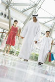 A Middle Eastern man with two children in a shopping mall — Stock Photo