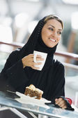 A Middle Eastern woman enjoying a meal in a restaurant — Stock Photo