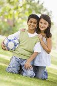 Zwei kinder spielen fußball im park — Stockfoto