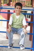 Boy sitting on climbing frame — Stock Photo