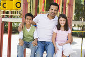 Father with children in playground — Stock Photo