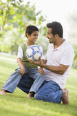 Father and son playing football — Stok fotoğraf