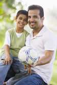Father and son playing football together — Stok fotoğraf
