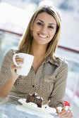 Woman enjoying snack at cafe — Stock Photo