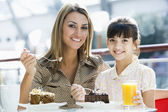 Mother and daughter eating cake in cafe — Stock Photo