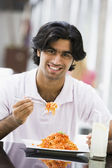 Man eating plate of pasta at cafe — Stock Photo