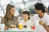 Family enjoying snack at cafe — Stock Photo