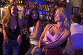 Three young women enjoying drinks together at a nightclub — Stock Photo