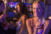 Three young women enjoying drinks at a nightclub — Stock Photo