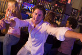 Young man in nightclub approaching camera with arms outstretched — Stock Photo
