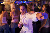 Young man in nightclub showing off for the camera — Stock Photo