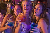 Three young women with drinks in a nightclub — Stock Photo