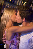 Young couple kissing in a nightclub — Stock Photo