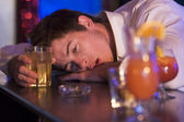 Drunk young man resting head on bar counter — Stock Photo