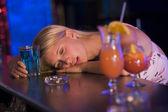 Dronken jonge vrouw hoofd rustend op toog — Stockfoto