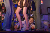Braga olhando três mulheres jovens dançando no bar balcão — Foto Stock