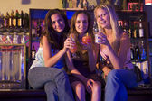 Three young women sitting on a bar counter, enjoying cocktails — Stock Photo