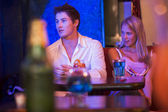 Young woman looking at a young man in a nightclub — Stock Photo