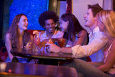 Group of young adults in a nightclub talking and laughing — Stock Photo