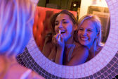 Two young women applying makeup in a nightclub bathroom — Stock Photo