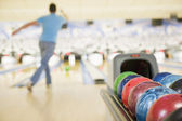 Bowling ball machine with man bowling in the background — Stock Photo