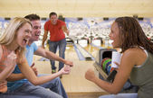 Four young adults cheering in a bowling alley — Stock Photo