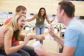 Four young adults laughing and gesturing in a bowling alley — Stock Photo