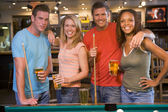 Two young couples standing beside a pool table in a bar — Stock Photo