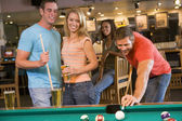 Young adults playing pool in a bar — Stock Photo