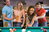 Young man teaching a young woman to play pool — Stockfoto