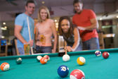 Young couples playing pool in a bar (focus on pool table) — Stock Photo