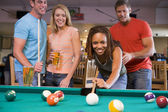 Young man teaching a young woman to play pool — Stock Photo