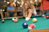 Young woman playing pool in a bar (focus on pool table) — Stock Photo