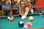 Young woman playing pool in a bar — Stock Photo