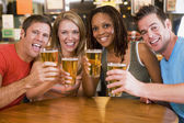 Group of young friends in bar toasting the camera — Stok fotoğraf