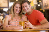Happy young couple having beers at a bar — ストック写真