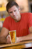 Young man relaxing at a bar with a beer — Stok fotoğraf