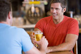Two men toasting beer in a bar — Stock Photo