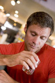 Young man at bar staring forlornly into drink — Stock Photo
