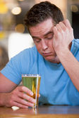Young man with beer falling asleep at bar — Stock Photo
