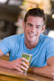 Young man enjoying a beer at a bar — Stock Photo