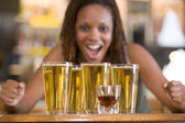 Young woman staring excitedly at a round of beers — Stock Photo